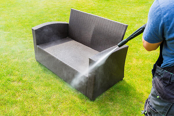 A professional cleaner washing down an outdoor couch.