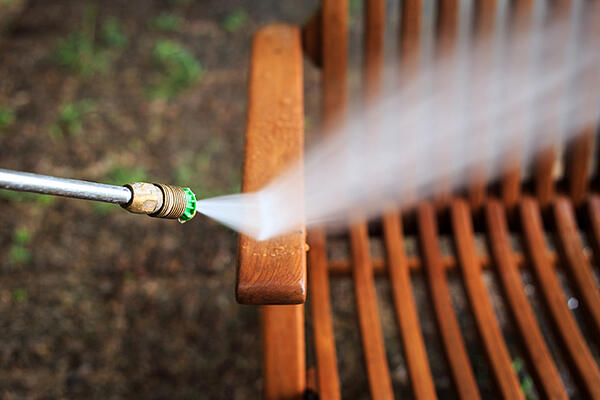 A hose spraying water on a piece of outdoor furniture
